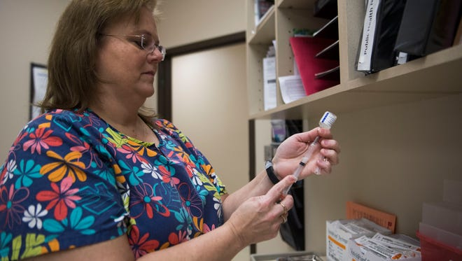 Registered Nurse Denise Morris prepares a flu shot to administer to patient Sandra McWilliams at the Knox County Health Department in Knoxville Thursday, Jan. 11, 2018.