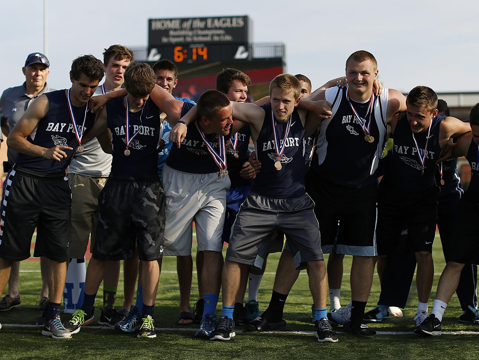 Bay Port track and field teammates huddle up before receiving the championship trophy for winning the Division 1 team title.