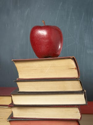 close up of books, apple and blackboard in classroom