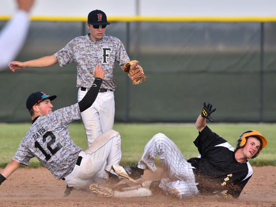 Frontier's Zeb Davis shows the umpire the ball after