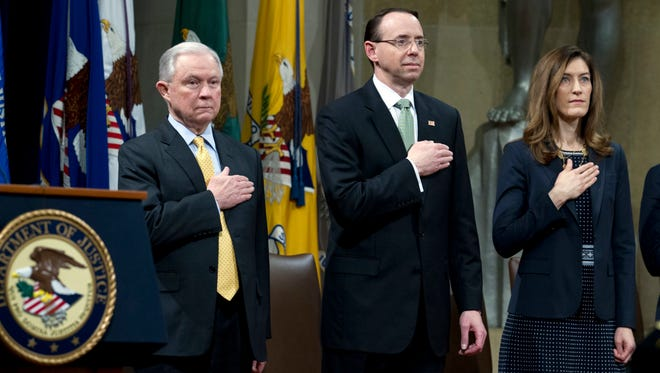 Attorney General Jeff Sessions accompanied by Deputy Attorney General Rod Rosenstein and Associate Attorney General Rachel Brand, listen to the national anthem during the opening ceremony of the summit on Efforts to Combat Human Trafficking at the Department of Justice in Washington, Feb. 2, 2018.