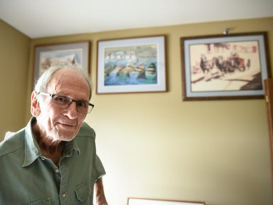 Mick Benson stands in front of some of the artwork