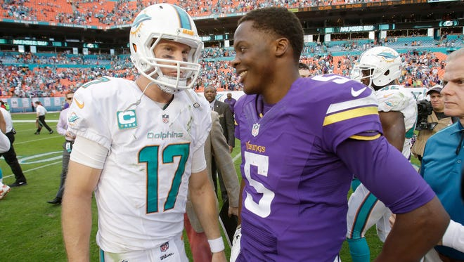 Miami Dolphins quarterback Ryan Tannehill (17) and Minnesota Vikings quarterback Teddy Bridgewater (5) talk after the Dolphins defeated the Vikings 37-35 in an NFL football game, Sunday, Dec. 21, 2014, in Miami Gardens, Fla. (AP Photo/Wilfredo Lee)