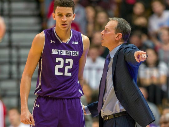 Northwestern head coach Chris Collins, right, talks with forward Pete Nance (22) during a break in the first half of an NCAA college basketball game against Indiana in Bloomington, Ind.