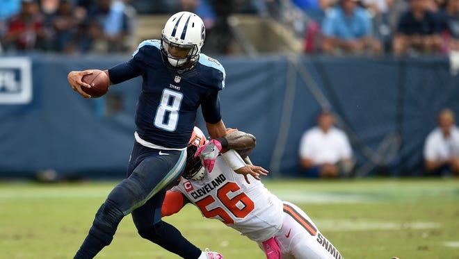 Titans quarterback Marcus Mariota (8) gets away from Browns inside linebacker Demario Davis (56) in the second half of last season's game.