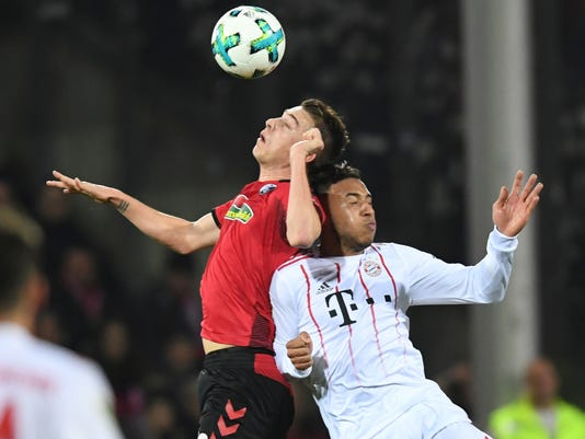 Freiburg's Janik Haberer, left, and Munich's Corentin Tolisso challenge for the ball during the German Bundesliga soccer match between SC Freiburg and Bayern Munich, in Freiburg, Germany, Sunday, March 4, 2018. (Patrick Seeger/dpa via AP)