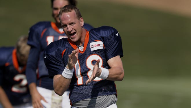 Denver Broncos' Peyton Manning claps for the music choice played during NFL football training camp on Monday, July 28, 2014, in Englewood, Colo.