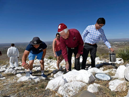"New Mexico State University Chancellor Garrey Carruthers, center, is joined by Kevin Prieto, right, president of Associated Students of NMSU, to help paint the ""A"" on Tortugas Mountain on April 3, 2018."