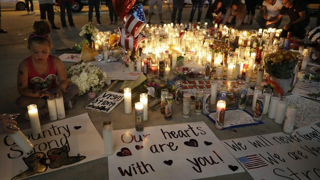 A girl places candles at a memorial for victims of the mass shooting Tuesday in Las Vegas.