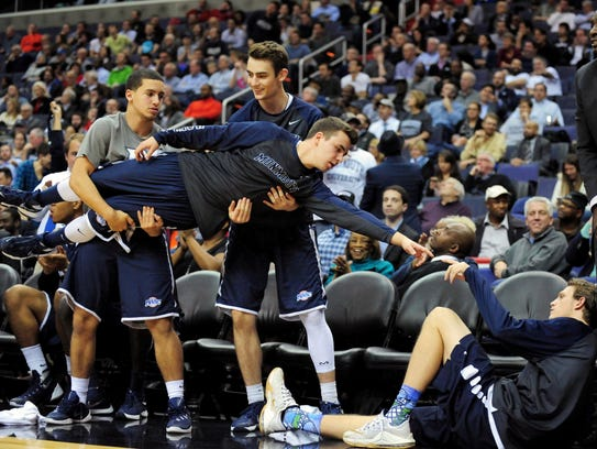 Monmouth Hawks bench players celebrate after a three