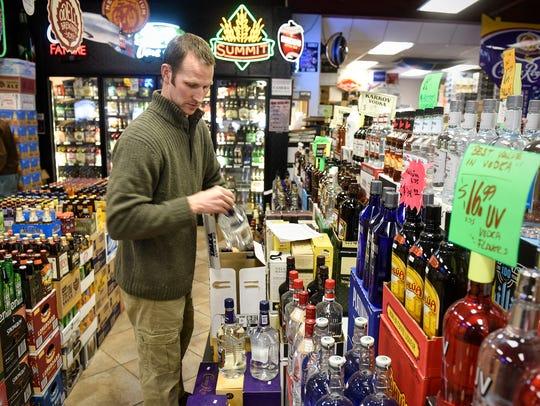 David Vos stocks bottles of liquor Monday, Feb. 27,