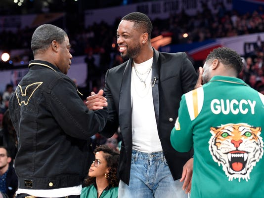 Actor Tracy Morgan, left, greets Dwyane Wade, center, of the Miami Heat, and actor Kevin Hart during the NBA All-Star basketball 3-Point contest, Saturday, Feb. 17, 2018, in Los Angeles. (AP Photo/Chris Pizzello)