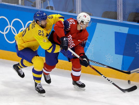 Viktor Stalberg (25), of Sweden, and Henrik Odegaard (42), of Norway, battle for the puck during the first period of the preliminary round of the men's hockey game at the 2018 Winter Olympics in Gangneung, South Korea, Thursday, Feb. 15, 2018. (AP Photo/Matt Slocum)