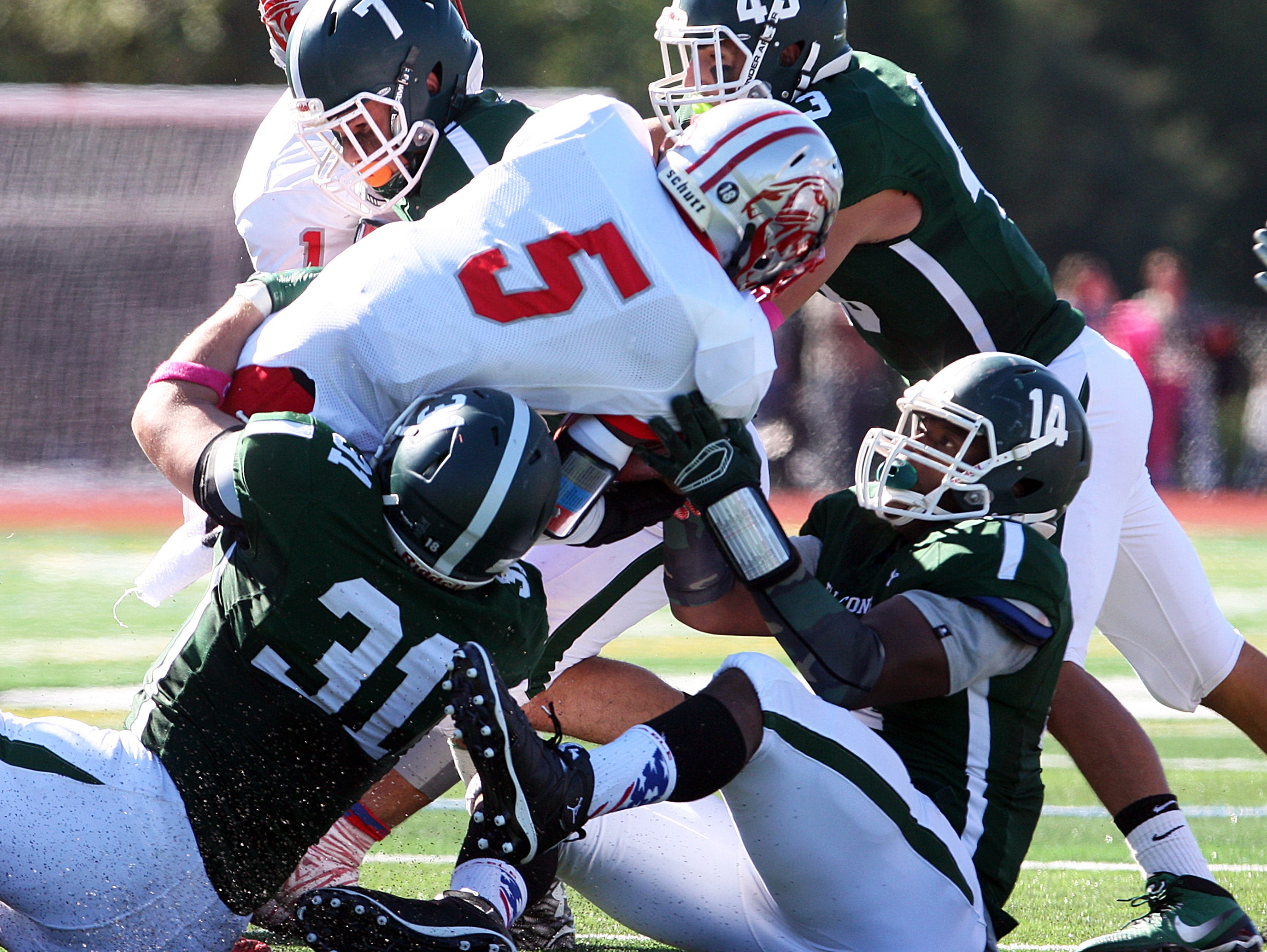Action photos from the Perth Amboy High School at St. Joseph football game held at St. Joseph's new turf field in Metuhen on Saturday October 10, 2015. Here Perth Amboy's # 5 (center)- Hakeem Guthrie is taken down by St. Joseph's # 31 (left)- Luke Yakely, # 14 (right)- Roderic Javier, # 7 Mitch Epstein and # 43 Joe Papa for a loss of yardage during the 1st half of play.