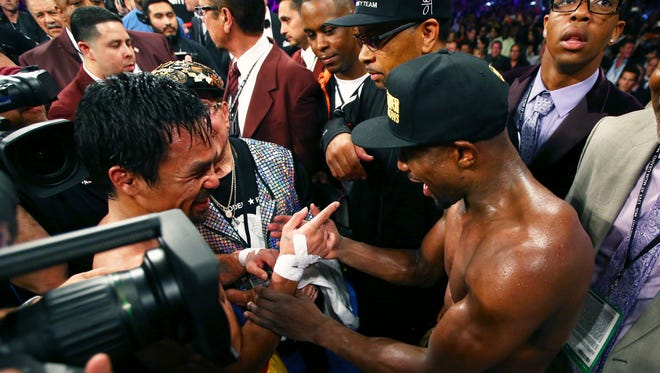 Floyd Mayweather (right) talks with Manny Pacquiao as celebrates after his welterweight championship bout at MGM Grand Garden Arena.