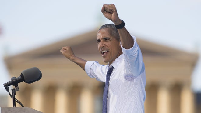 President Obama raises his arms in the air during a rally for Democratic presidential nominee Hillary Clinton at Eakins Oval in Philadelphia Tuesday.