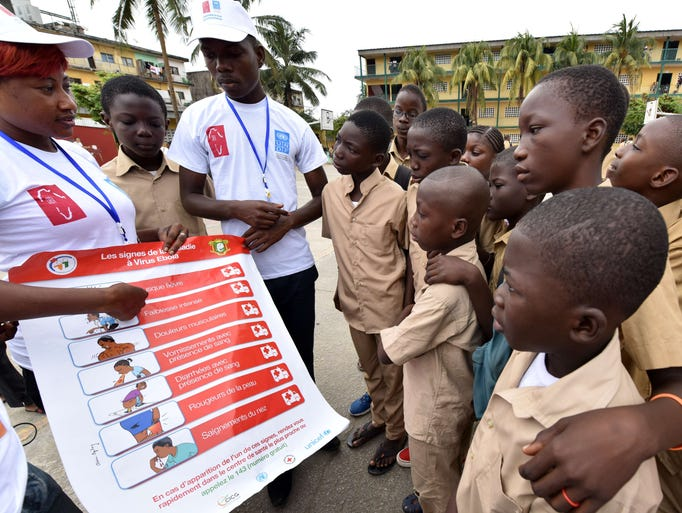Volunteers from the United Nations Development Program conduct a meeting with students to raise awareness about the symptoms of the Ebola virus at the Sainte Therese school on Sept. 15 in Koumassi, Ivory Coast.