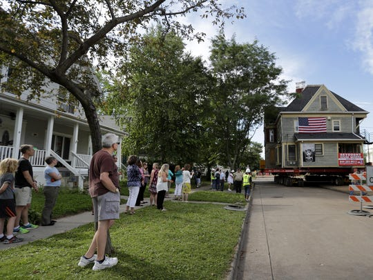 Spectators watch Tuesday as a house is moved along
