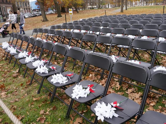 Pedestrians pass by the COVID-19 Empty Chair Memorial on display at Campagnone Common in Lawrence, Mass., on Wednesday. Each chair represents a person from Lawrence who has died with the coronavirus. Massachusetts hit 10,015 confirmed coronavirus deaths Thursday.