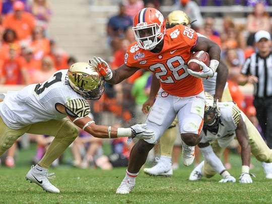 Clemson running back Tavien Feaster (28) carries past Wake Forest defensive back Jessie Bates III (3) during the 2nd quarter on Saturday, October 7, 2017 at Clemson's Memorial Stadium.