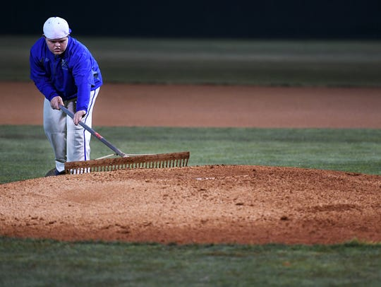 Eli Quinn helps prepare the pitcher's mound before the start of Game two of the Class AA baseball game Tuesday. Riverside defeated Grundy County 5-4.