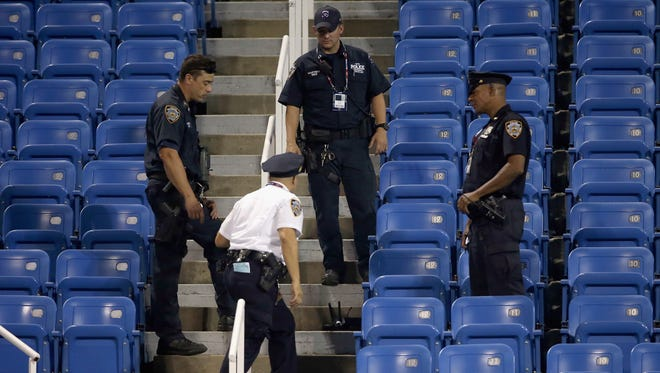 Police surround a remote-controlled drone that crashed into the seats at Louis Armstrong Stadium.