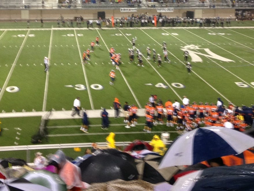 Fans stay dry during a Brandeis High School football game.