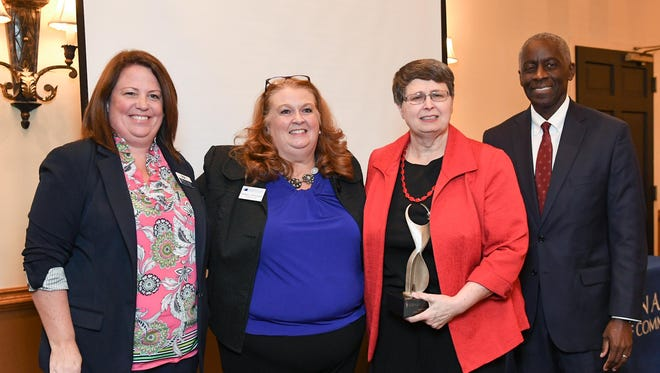 Faith Line, middle right, Director of the Anderson County Library, is awarded the ATHENA Award by Lauren Lindsey, left, Client Relations Coordinator of PIP Printing, Pamela Christopher, middle left, and Mayor Terence Roberts, right, during the Anderson Area Chamber of Commerce small business luncheon at Tucker's Restaurant in Anderson on Thursday.
