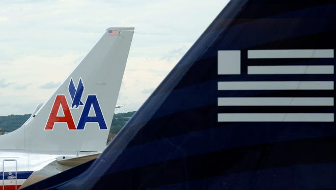 The file photo from Aug. 13, 2013, shows a US Airways and an American Airlines plane at Washington's Ronald Reagan National Airport.