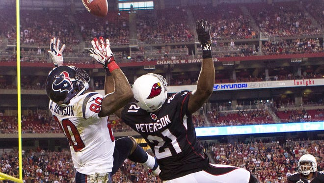 Cardinals cornerback Patrick Peterson battles Houston receiver Andre Johnson for a pass on Sunday, Nov. 10, 2013, in Glendale.