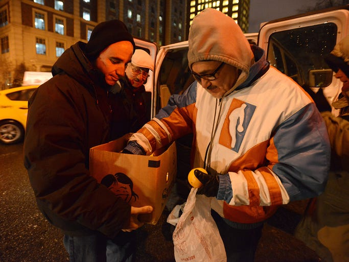 Isaac Simon, left, gives food to a homeless person Dec. 17 in New York City. Simon, a UBS personal wealth adviser, works with Coalition for the Homeless to bring food and clothing to people living on the streets.