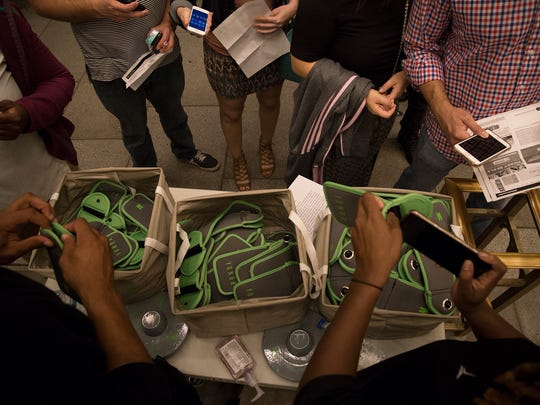 Event-goers line up as their mobile devices are locked into Yondr pouches.