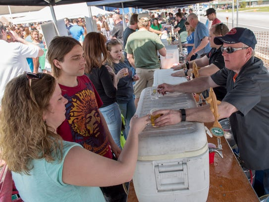 Guests walk under a tent to get samples of beer during