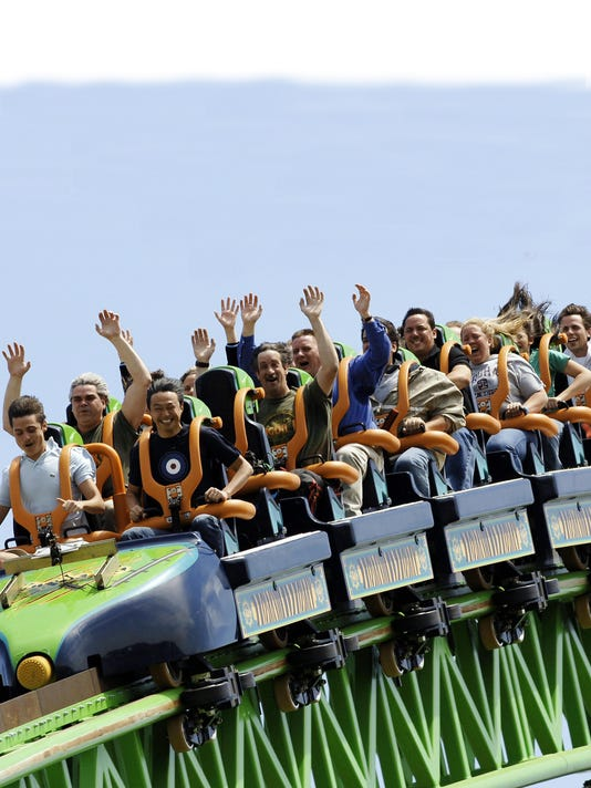 Riders raise their arms as they travel t