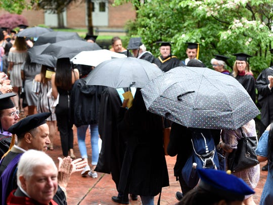 Graduates of the Passaic County Community College's Class of 2018 march through the rain into the auditorium for commencement in Paterson, NJ on Thursday, May 17, 2018.