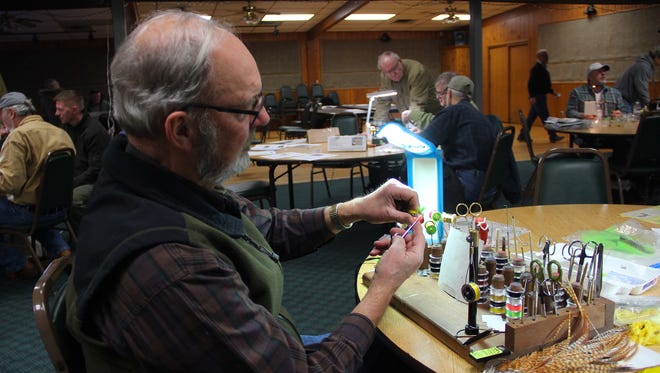 Ira Giese of Wautoma ties a Hart Washer at a meeting of the Central Wisconsin chapter of Trout Unlimited. The dry fly, often tied in green and gold, is named after former Green Bay Packers player Doug Hart.