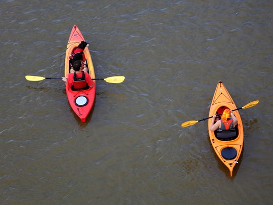 A pair of kayaks float along the Ohio River near the Public Landing.