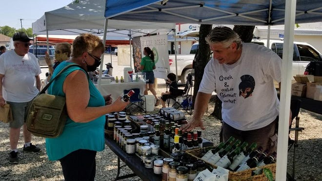 A vendor at the Railcar Farmers Market in Van Alstyne explains his products to a shopper. The market it held Tuesdays in downtown Van Alstyne.