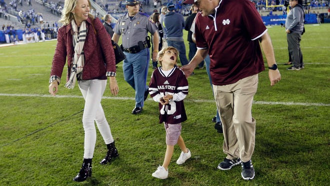 Oct 25, 2014; Lexington, KY, USA; Mississippi State Bulldogs head coach Dan Mullen, his wife Megan and son Canon walk off the field after the game against the Kentucky Wildcats at Commonwealth Stadium. Mississippi State defeated Kentucky 45-31. Mandatory Credit: Mark Zerof-USA TODAY Sports