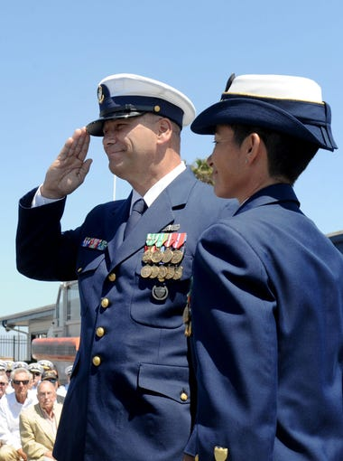 Lt. Thomas Wieland, left, the commanding officer of the U.S. Coast Guard Station at Channel Islands Harbor salutes his replacement Officer-in-Charge Senior Chief Boatswain's Mate Kevin Wyman as Sector Cmdr. Capt. Charlene Downey watches at the change-of-command ceremony last week.