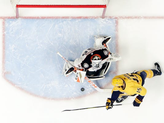 Anaheim Ducks goalie John Gibson, left, blocks a shot against Nashville Predators right wing Craig Smith, right, in the first period of an NHL hockey game Thursday, March 8, 2018, in Nashville, Tenn. (AP Photo/Mark Humphrey)