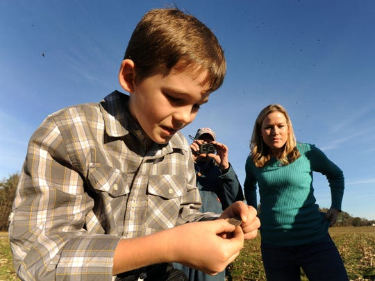 Bobby Grangier, 10, uses his fingertips to remove dirt from the surface of a 1772 English copper coin as his grandfather, Ronnie Grangier, takes photos and his mother, Sarah, watches.