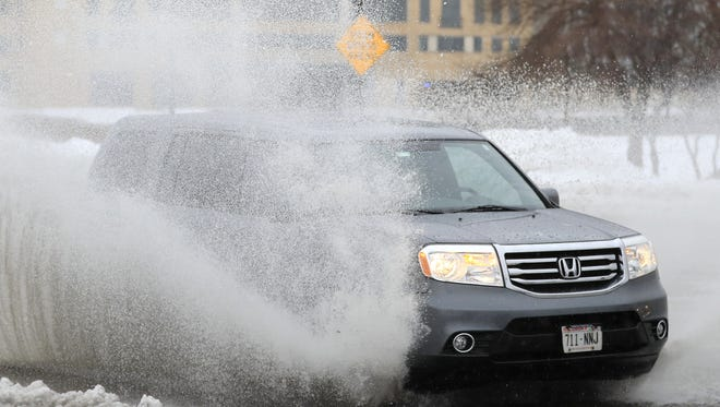A vehicle drives through standing water Tuesday on Dousman Street in Green Bay.