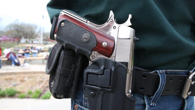 A chrome-plated handgun rests in the hip holster of Gary Kastrup of Newell, Iowa, during a pro-gun rally at the west terrace of the Iowa Capitol Building in Des Moines on Saturday, April 18, 2015.