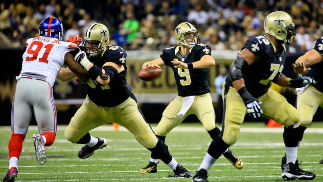 New Orleans Saints quarterback Drew Brees (9) looks to pass against the New York Giants during the second quarter of a game at the Mercedes-Benz Superdome.