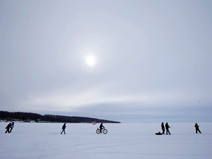 A winter sun offers little warmth to walkers and bicycle