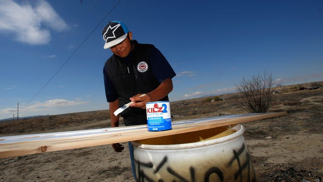 Denny Hale, 19, paints pieces of wood while working on his home in Hogback on Friday.