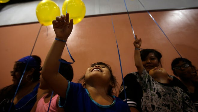 Tahliyah Thomas plays with a balloon June 25 with her family during the Ashlynne Mike Awareness Fundraiser at the Walter Collins Event Center in Upper Fruitland.