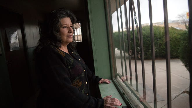 Debbie Magruder, manager and director at the Well Recovery Club, looks out a window on Thursday in Farmington. Magruder said she looks across the street for people who need things like a warm cup of coffee or gloves as they wait to for a place to stay at The Roof.