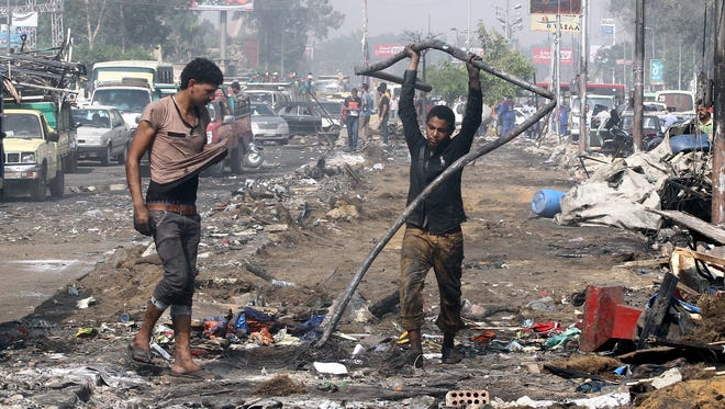 People salvage items left by protesters Thursday, a day after the clearing of a sit-in in Cairo.